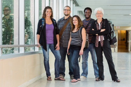 Grad students standing with college professor photo