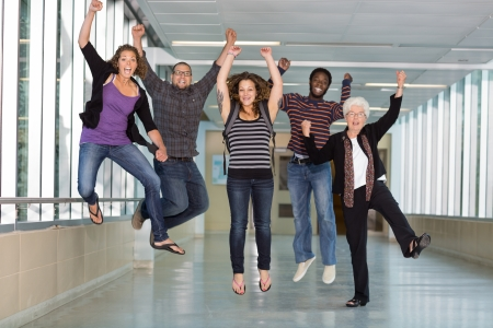Full length portrait of excited multiethnic university students jumping in corridor with professor photo