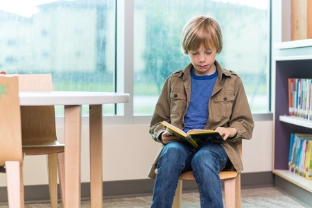 public library: Schoolboy reading book on chair in library Stock Photo