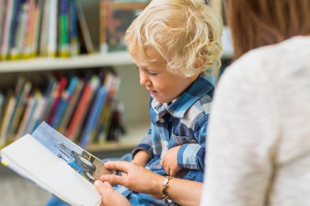 public library: Schoolboy with teacher looking at picture book in library Stock Photo