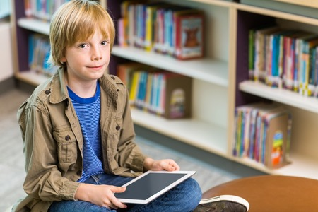 Portrait of young boy with digital tablet in library photo
