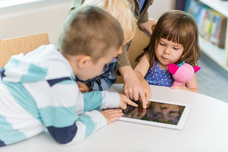 Cute girl with friends using digital tablet at table in school library photo
