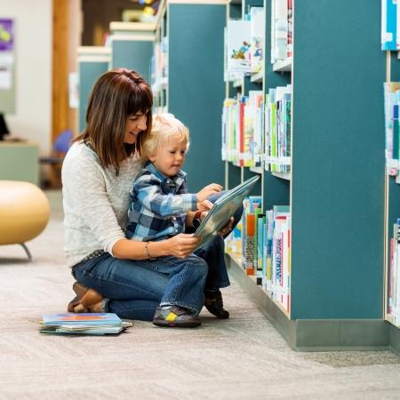 niños leyendo: Longitud total de profesor y el libro de lectura escolar por el estante en la biblioteca