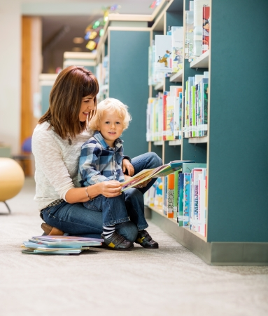 Portrait of elementary student with teacher reading book by bookshelf in library photo