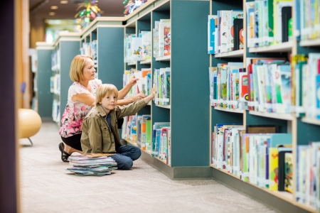 school room: Portrait of young boy with teacher selecting books from bookshelf in library