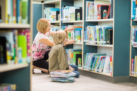 primary school: Mature teacher assisting boy in selecting books from bookshelf in library