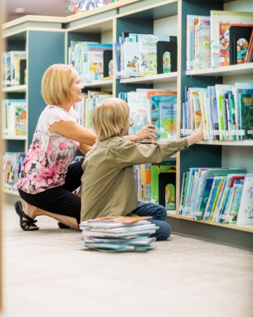 Mature teacher and boy selecting books from bookshelf in library photo