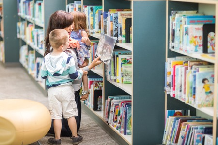 Young teacher with children selecting book from bookshelf in library photo