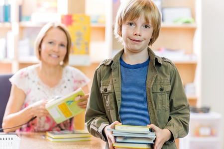 Portrait of happy young boy checking out books from library with librarian in background photo