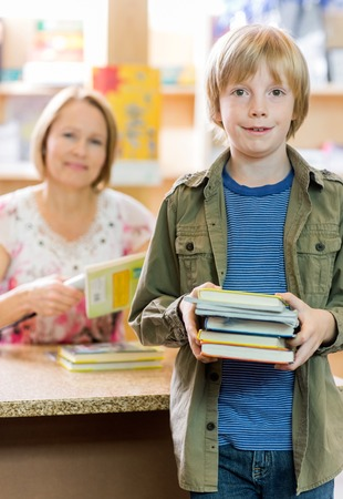 Portrait of happy schoolboy checking out books from library with librarian in background photo
