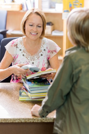 Mature female librarian scanning books at counter while boy standing in library photo