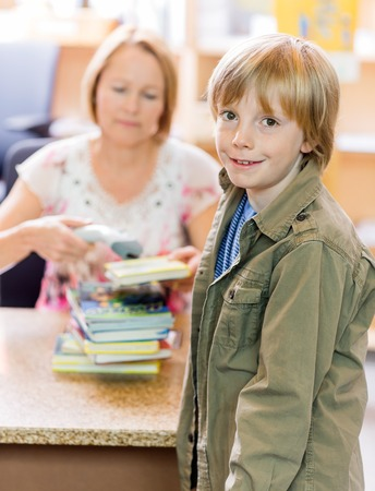 public library: Portrait of young boy with librarian scanning books at checkout counter in library