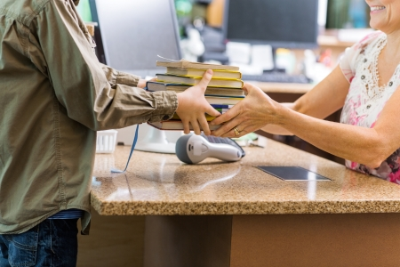 Midsection of young boy giving books to librarian at checkout counter in library Stock Photo