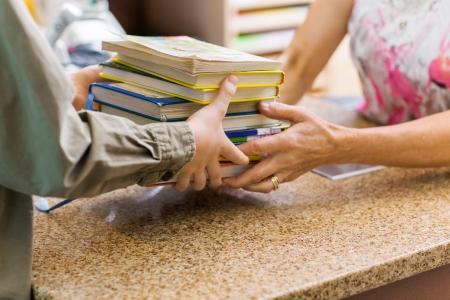 Image recadrée de bibliothécaire femmes prenant des livres de garçon au comptoir de caisse dans la bibliothèque Banque d'images