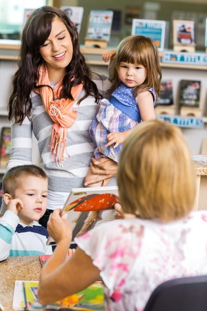 public library: Mother and children looking at librarian showing book in library