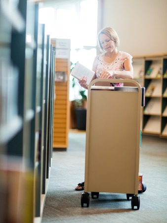 put away: Mature female librarian working in library Stock Photo