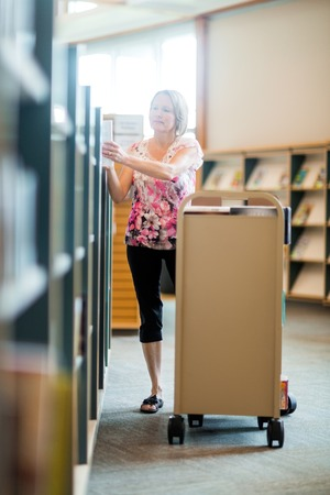 put away: Full length of mature female librarian arranging books in library