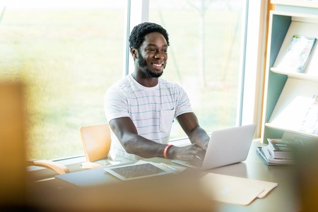 Smiling university student using laptop while studying in library photo