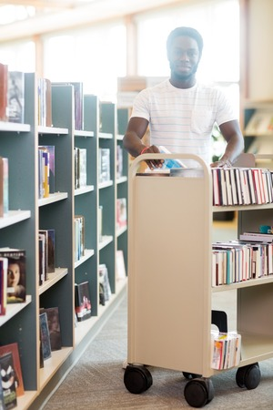 put away: Portrait of happy male librarian with trolley of books working in library Stock Photo