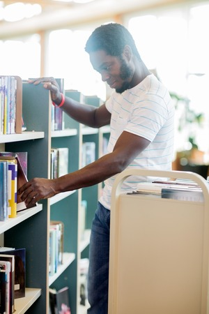 put away: Young male librarian arranging books in library