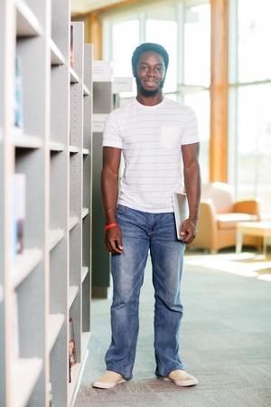 bookshelf digital: Full length portrait of male student with digital tablet standing by bookshelf in library Stock Photo