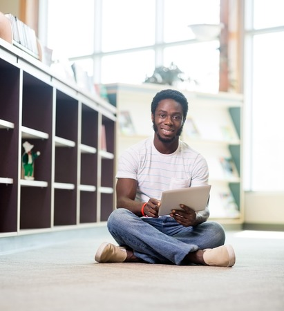 Full length portrait of confident male student with digital tablet while sitting on floor at library photo