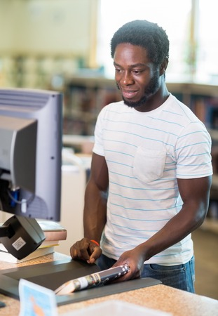 African American male librarian working at counter in bookstore photo