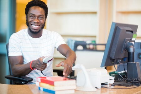 Portrait of happy male librarian scanning books at desk in library photo