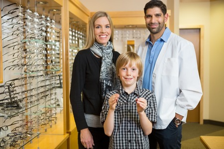Portrait of boy holding glasses while standing with mother and optician in store photo