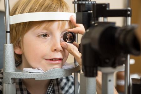 Closeup of male opticians hand checking boys eye with lens in store photo