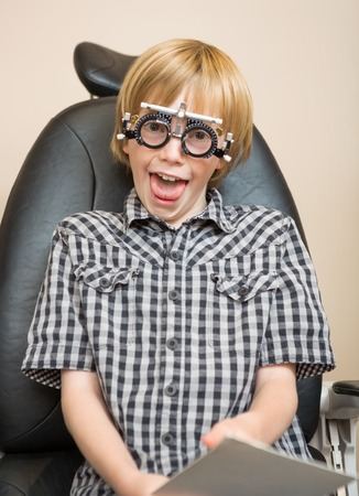 Portrait of preadolescent boy with trial frame making funny face at optician photo