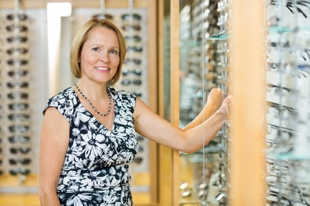Portrait of happy female customer selecting glasses in optician store photo