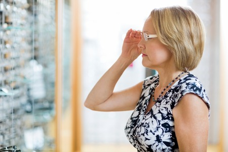 Mature woman trying on eyeglasses in optician store photo