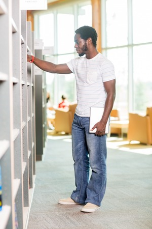 Full length of male student with digital tablet selecting book in bookstore photo