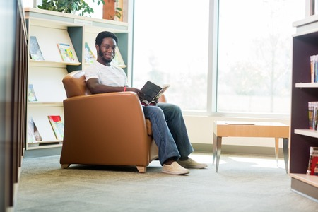 Full length portrait of young African American student reading book in library photo
