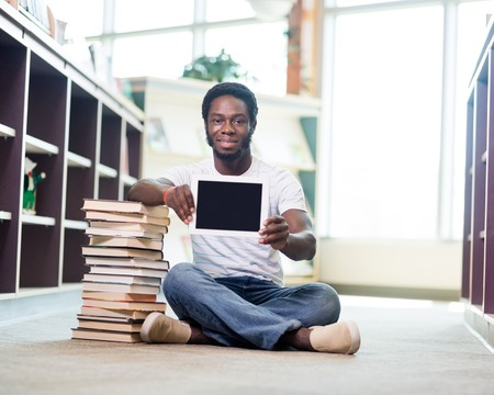 Full length portrait of confident student with stacked books showing digital tablet while sitting on floor at library photo