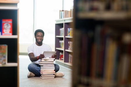 Full length portrait of young male student with digital tablet and books sitting on floor at library photo