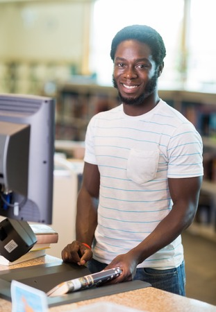 Portrait of happy male librarian scanning books at counter in library photo
