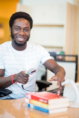 Portrait of smiling young librarian scanning books at library desk photo