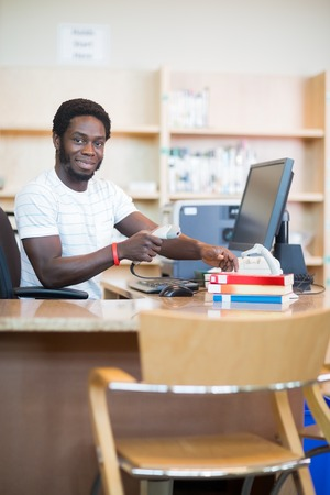 Portrait of young male librarian scanning books at desk in library photo