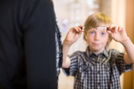 spectacle: Preadolescent boy holding spectacles with mother in foreground at shop Stock Photo