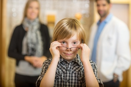 Portrait of boy trying eyeglasses with optometrist and mother standing in background at store photo