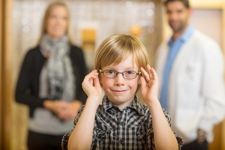 Portrait of smiling boy trying glasses with optometrist and mother standing in background at store photo