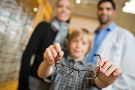 Little boy showing glasses while standing with mother and optician in store photo