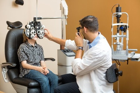 ophthalmologist: Mid adult male optometrist examining preadolescent boys eyes in clinic