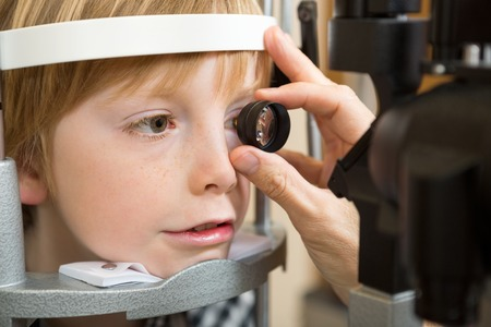 Closeup of male opticians hand examining boys retina with lens in clinic photo