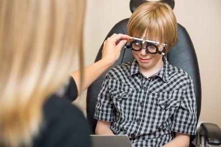 Female optician determining prescription values with trial frame for preadolescent boy in store photo