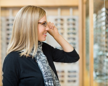 Side view of beautiful woman trying on glasses in optician store photo