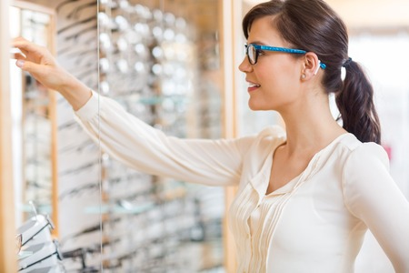 Beautiful young woman buying new glasses at optician store photo