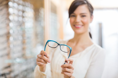 Portrait of happy young woman showing glasses at store photo